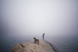 Girl and dog on foggy cold peninsula stretching into a winter lake.