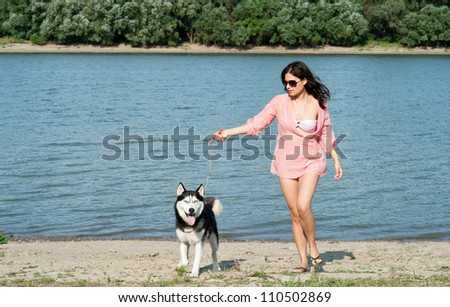 girl and dog walking along the coast