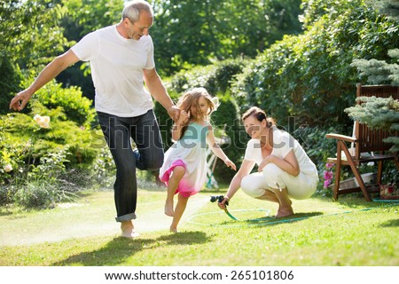 Girl and grandparents playing and waterin garden