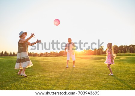 Girl and grandparents playing ball. People having fun outdoors, summer.