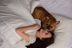 girl and her dog french bulldog sleep in bed