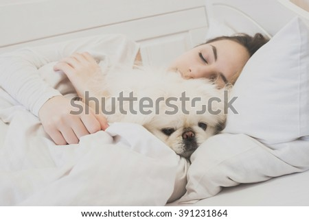 Girl and her dog in the bed. #391231864