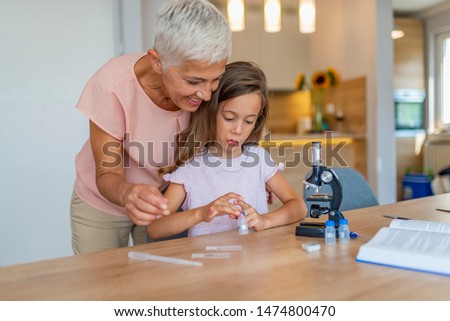 Girl and her grandmother doing scientific experiment. Preparation for scientific experiment with my grandmother. Portrait of happy girl and her grandmother at home