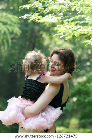 Girl and her mother are relaxing in the summer park