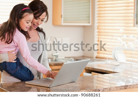 Girl and her mother using a laptop in a kitchen