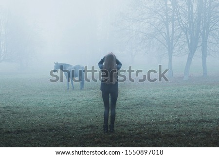 Girl and horse. Black Horse. Paranormal world. Strange forest in a fog. Mystical atmosphere. Dark wood. Mysterious road. Gothic witch. Background wallpaper. Scary forest trees in a fog.