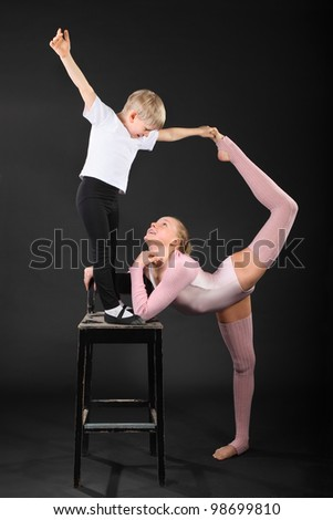 Girl and little boy gymnast took graceful pose at bark chair in black studio