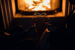 girl and  man at the fireplace drink wine