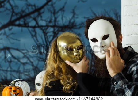 Girl and man hide face with masque. Woman with long blond hair and bearded hipster in mask at window. Carnival, masquerade, holiday celebration. Decoration, amusement, disguise, pretense concept.