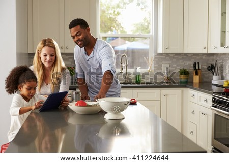 Girl and mixed race parents use tablet computer in kitchen