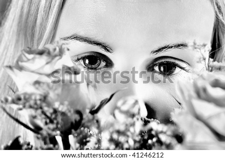 Girl and roses : Beautiful young woman\'s face fragment with colour roses over (Black and White).
