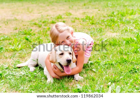 girl and she lablador, hugging in the park lying on the grass