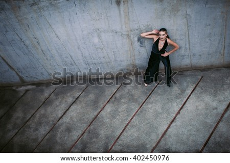 girl and the geometry. Beautiful lady in black dress is standing next to the wall and watching parallel lines on the floor #402450976