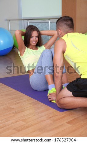 Girl and trainer engaged in fitness room