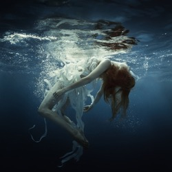 Girl and white ribbons under water