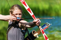 Girl archer shooting with bow and arrow in the nature