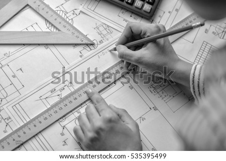 Girl architect draws a plan, graph, design, geometric shapes by pencil on large sheet of paper at office desk. #535395499