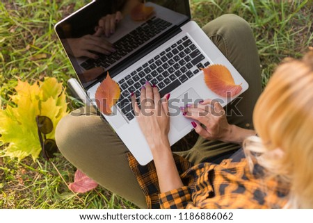 Girl are typing on a laptop keyboard on a autumn background with fallen leaves and green grass. Sunglasses.  Online work, freelancing. Side top View #1186886062