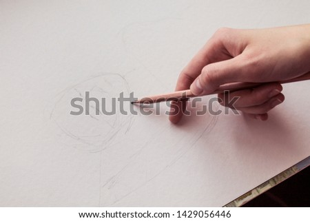 Girl artist draws a sketch with a pencil. Hand drawing. Drawing a portrait. Close-up