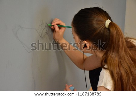 Stock Photo girl artist draws on the wall drawing,