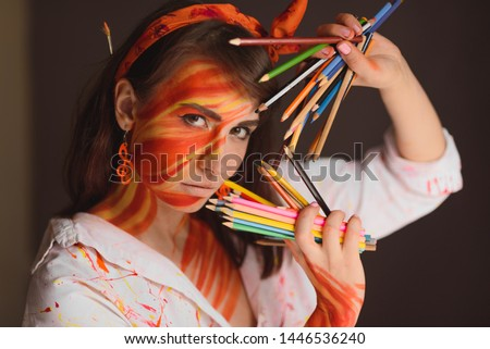 girl artist in a white shirt and a picture on the skin in the form of fire with colored pencils in her hand