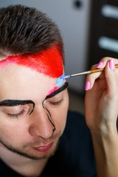 Girl artist paints on a man�s face. Face painting on the skin. Portrait of a young man with colored paint on a yellow background. Professional Makeup Fantasy Art Makeup