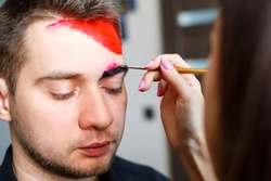 Girl artist paints on a mans face. Face painting on the skin. Portrait of a young man with colored paint on a yellow background. Professional Makeup Fantasy Art Makeup