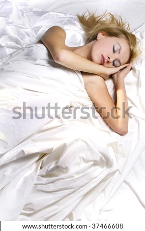 Girl asleep in bed wrapped in white sheets