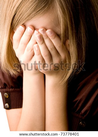 girl at age of thirteen covers her face with her hands closeup