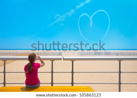 Girl at beach on bright sunny day viewing heart shaped skywriting