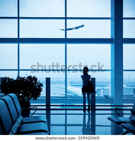 girl at the airport window and flight departure