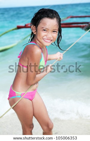 Girl at the beach pulling a rope from a wooden boat.