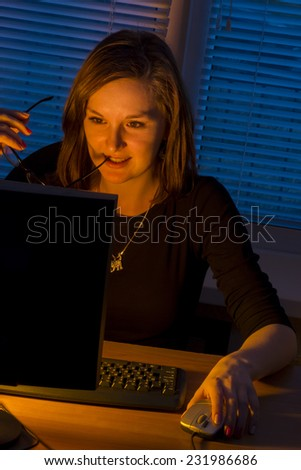 girl at the computer in the office at night\woman working overtime at night. computer work at night, in the light of the monitor