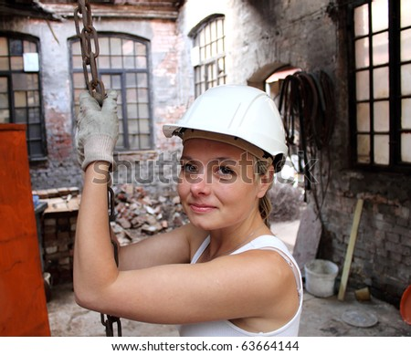 girl at work on a construction site, holding a chain