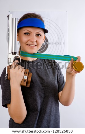 girl athlete on bullet shooting keeps in hand gun and medal