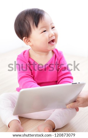 Girl baby happy play game with tablet PC. asian child smile look her mother