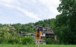 Girl Backpacker alone visiting old village on a trip in Bulgaria. Caucasian woman with hat standing searching and looking in front of mountain town. Eastern balkan calm rural destination