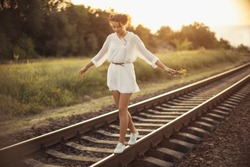 Girl balancing on train rail. Attractive young woman walking outdoors
