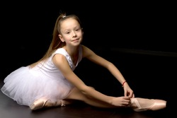 Girl ballerina puts on pointe shoes. The concept of dancing.