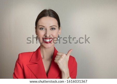 Girl bank worker in a red blazer smiles a snow-white smile showing class gesture. Isolated portrait of smiling business woman