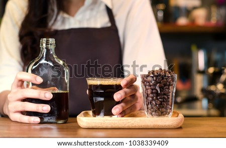 Girl barista bartender waiter in uniform making coffee,Asian Barista woman Cold brew coffee in glass bottle to a cup glass in the coffee shop. people with barista in cafe concept.