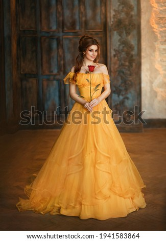 Girl beauty fantasy princess in yellow long historical, medieval silk dress holding flower red rose in her hands. Background of old gothic castle room. Fairy tale bewitched queen. Happy woman smiles.