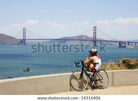 girl bicylist on cell phone near Golden gate bridge