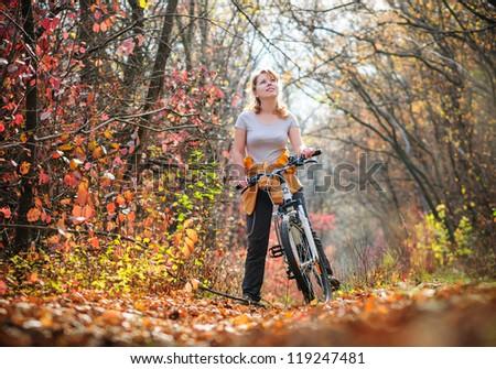 girl biking in autumn forest - stock photo