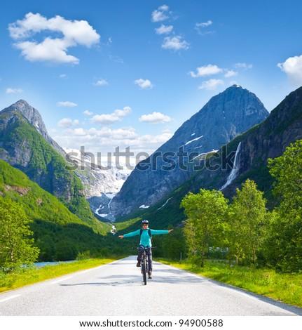 Girl biking in high mountains in Norway