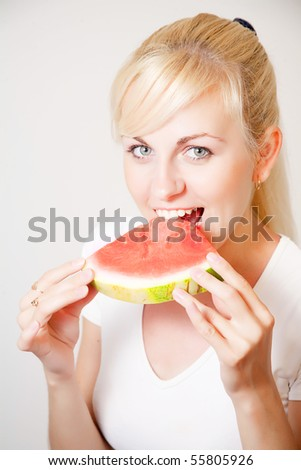Girl biting slice of watermelon