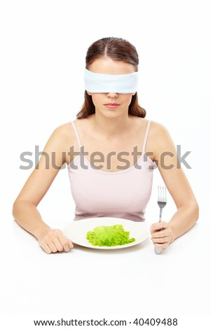 Girl blindfold sits before plate with salad leaf, isolated