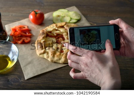 Girl blogger taking pictures of cooked food with their hands, vegetable crackers, cooking blog, side light