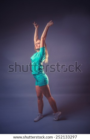 girl blonde European appearance raised her hands up on a gray background, charge, sports retro