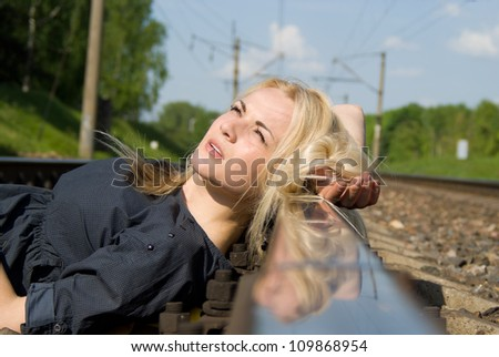 girl blonde put her head on the rails in nature